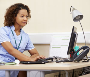 health care worker entering information at a computer